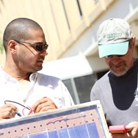 Professor Ronald Roedel works on a solar panel with another man.