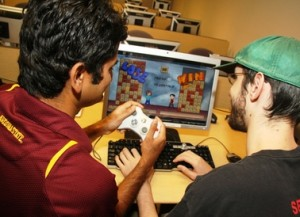 Computer gaming instructor Ashish Amresh (left) and computer science student Ryan Scott demonstrate the computer video game World Wide Words, designed to teach spelling to children in developing nations. It currently offers versions of the game in English, Spanish and Hindi. It's one of hundreds of games developed by student teams in ASU's computer gaming certificate program. Blaine Coury photo.