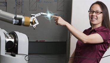 Veronica Santos, an assistant professor of mechanical engineering, demonstrates the capabilities of a robotic hand being developed in her Biomechatronics Lab.