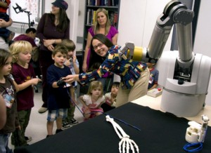 ASU assistant engineering professor Veronica Santos (at right) instructs preschool students how to use a sensor glove to control the fingers on a robot hand at the Biomechatronics Lab. (Photo: Jessica Slater/ASU)