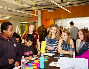 ASU engineering student teaching assistant Katelyn Keberle (third from left) looks on as ASU Preparatory Academy students go over the rules for a game called Decimal Dynasty, which requires players to answer math questions to make progress on a journey to a castle. Photo: Jessica Slater/ASU
