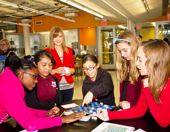 ASU engineering students Kelsey Stopkey (center) and Julia King (far right) gather with six-grade students from ASU Preparatory Academy to examine a prototype for a game called Battle Plates, designed to teach geological concepts related to plate tectonics. It was one of several toy and game designs the engineering students and youngsters collaborated on. Photo: Jessica Slater/ASU