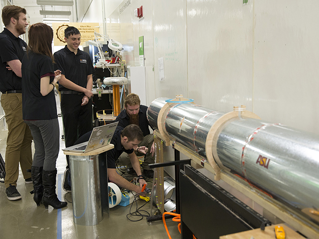 Members of the ASU Polytechnic Hyperloop Team prepare for a test run of their Hyperloop Pod prototype. Their design uses a fan and a compressor to create a cushion of air for levitation and linear electric motors to propel the pod forward. Photo by Nick Narducci/ASU
