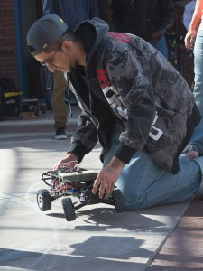 A student crouches down with a robotic car before a demonstration