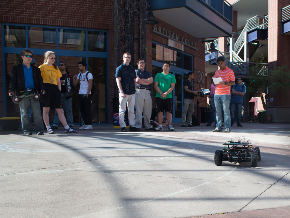 Students in Brickyard courtyard watch a demonstration of a self-navigating car