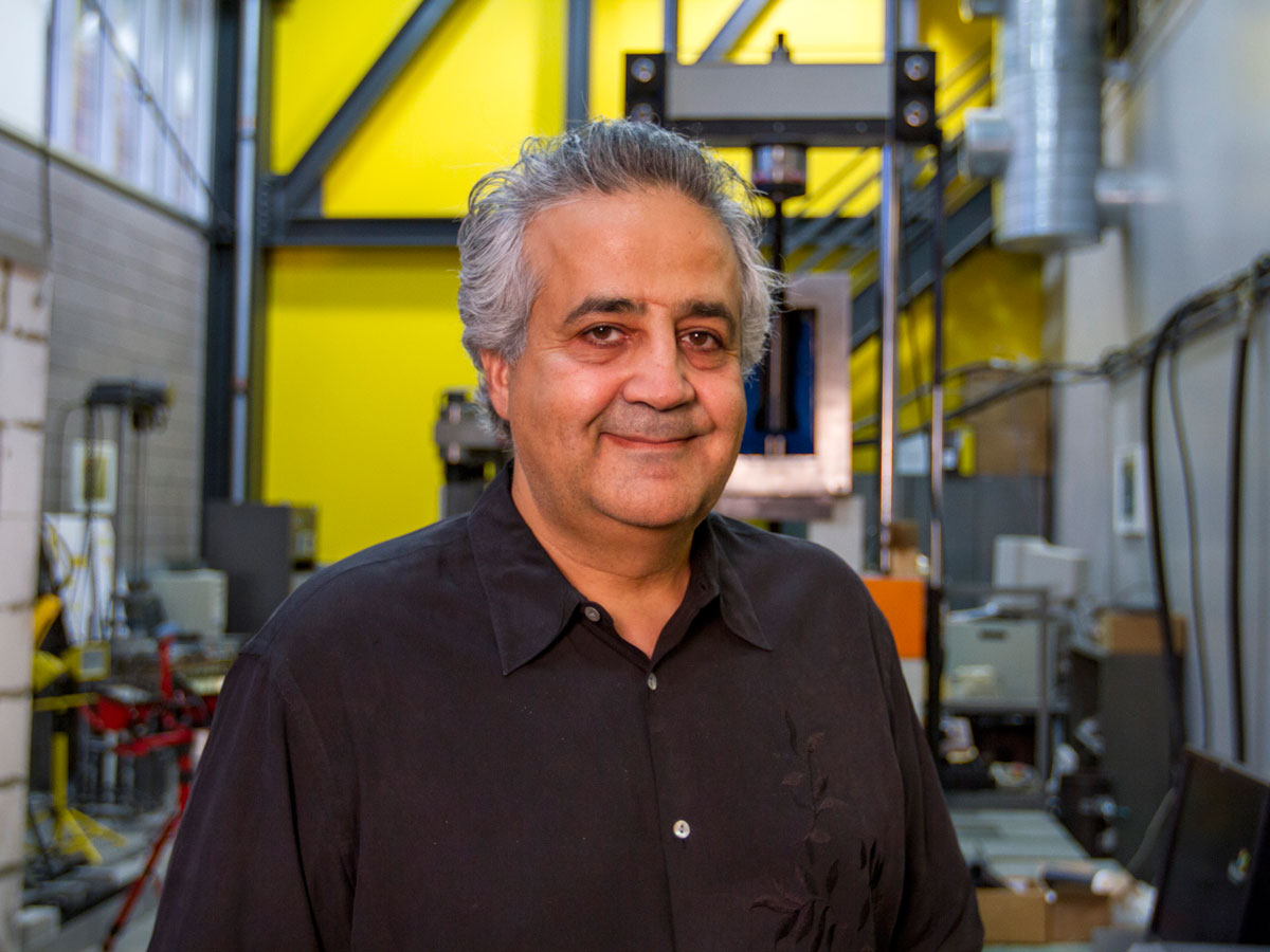 Barzin Mobasher stands in front of equipment in the Structural Mechanics and Infrastructure Materials Laboratory.