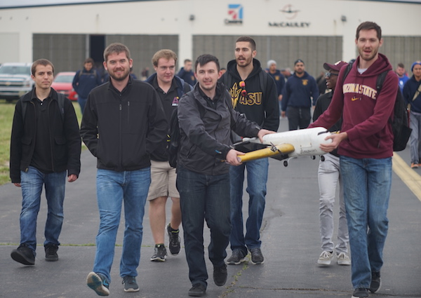 Air Devils team members carry their Manufacturing Support Aircraft to the starting line for one of the Design/Build/Fly competition flight missions. Pictured are (back row, left to right) Ivan Kruts, Nathan Stone, Brendan Hernandez, Walter Bonar; (front row, left to right) Jeffrey Kirkman, AJ Verbin, Ben Anderson.
