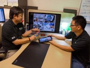 Gail-Joon Ahn (left) demonstrates some of the SEFCOM lab research with a student.
