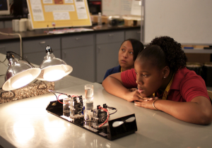 Middle School students in a sustainable engineering lab watch a hydrogen fuel cell at work.