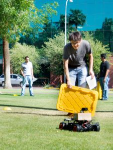 A student holds up a crate lid to test his car's ability to sense an obstacle in its path.