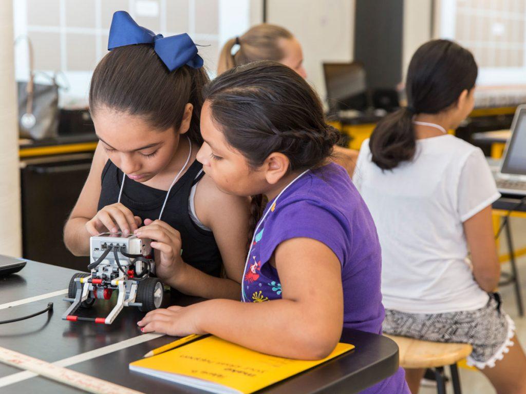 Two girls start up their robot to start testing their program.