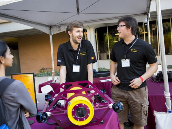 Electrical engineering student Michael Saxon, right, and Calvin Norman, a mechanical engineering major, chat while manning the Sun Devil Robotics Club exhibit at the Fulton Schools' Block Party, Oct. 22, 2016. Photographer: Jessica Hochreiter/ASU
