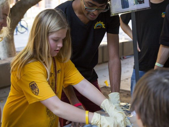 Researchers with Quantum Energy Sustainable Solar Technologies show a young guest the principles of silicon nitride deposition, used in the creation of solar panels, at the Fulton Schools' Block Party, Oct. 22, 2016. Photographer: Jessica Hochreiter/ASU