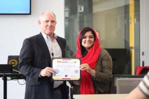 Kenneth Mulligan, professor for the U.S.-Pakistan Centers for Advanced Studies in Energy, presents Pakistani exchange scholar Nafeesa Irshad with her certificate of completion for the entrepreneurship portion of the USPCAS-E program.