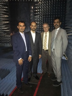 """Portrait of four men with a caption of """"KACST Chief Engineer Waleed Abduaziz Alomar, KACST Project Manager Turki A. Alanazi, ASU Principal Investigator Constantine A. Balanis and KACST Principal Investigator Hussein Nasser Shaman tour the ASU EMAC experimental facility during their February visit. Photo courtesy of Constantine Balanis."""""""
