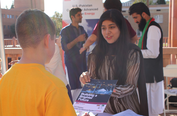 "Photo of student showing a brochure to a child with a caption of ""Farah Akram explains to members of the public what USAID's mission is in Pakistan at Tempe Night of the Open Door. Photographer Erika Gronek/ASU"""
