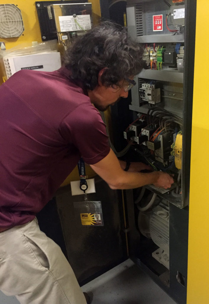 This photo shows ASU IAC student lead and mechanical engineering doctoral candidate Nicholas Fette examining a data logger on an HVAC system.