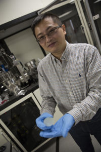 A man wearing glasses, a button-down shirt and blue gloves holds a small, semi-translucent disc in front of some scientific equipment. The caption reads: Yuji Zhao, an assistant professor in the School of Electrical, Energy and Computer Engineering, holds a gallium nitride wafer in his lab. Photographer: Pete Zrioka/ASU
