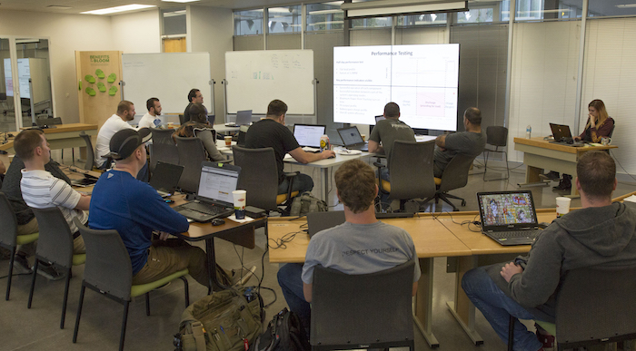 "A photo of students sitting in a classroom with a caption of ""Attendees of the microgrid bootcamp learn the ins and outs of microgrid setup, operation and optimization during one of the weeklong program's classes on the Polytechnic campus. Photographer: Pete Zrioka/ASU."""