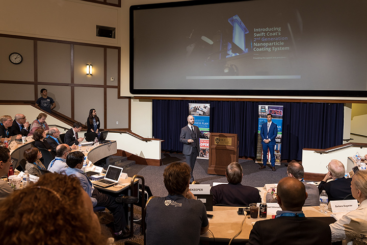 "Photo of two men making a presentation in a lecture hall with a caption of ""Peter Firth, center, and Jonathan Bryan pitch their startup at the Rice Business Plan Competition, held at Rice University in Houston, Texas, from April 6-8. Swift Coat advanced farther in the competition than any ASU team before, securing more than $70,000 with a fourth place finish and entrance into another entrepreneurial competition later this summer. Photo courtesy of Peter Firth"""