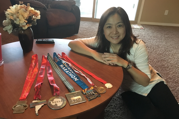 A woman poses with seven medals spread out across a coffee table. The caption reads: Sophie Olson displays her seven marathon medals, each from a different continent. What started as a challenge to get herself in shape grew dramatically when she decided to start a worldwide marathon tour. Photo courtesy of Sophie Olson