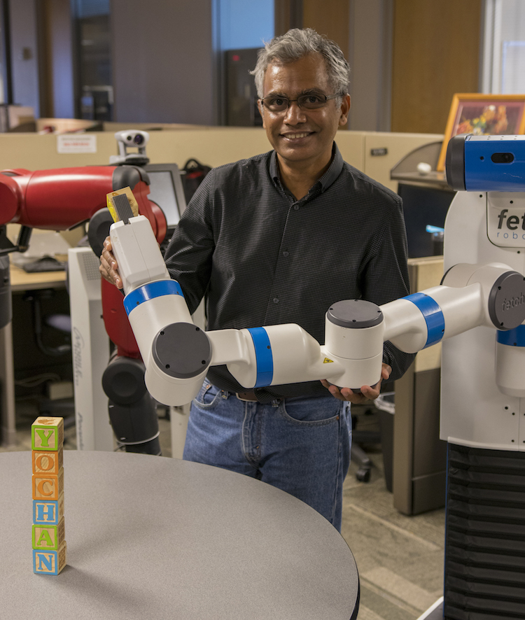"Photo of Professor Subbarao Kambhampati with one of the robots used in his lab team's research aimed at enabling effective collaboration between humans and intelligent robots. The wooden building blocks on the table spell out the name of the lab, Yochan, meaning ""thought"" or ""plan"" in the Sanskrit language. Photographer: Marco-Alexis Chaira/ASU"