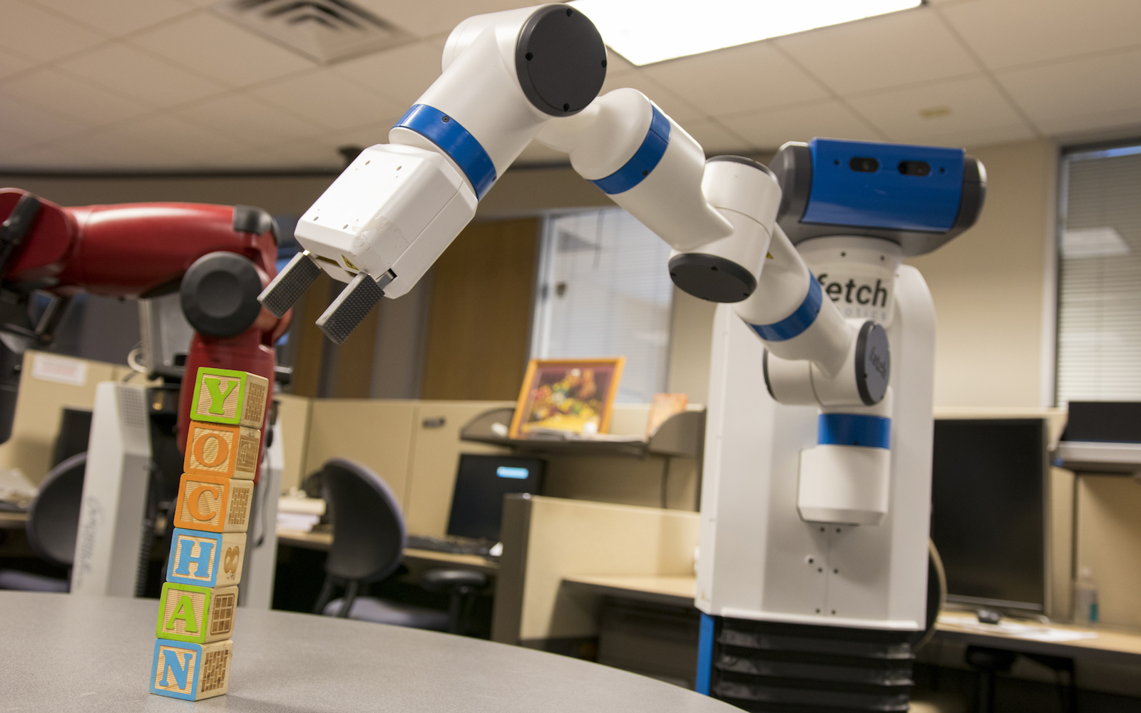 "Photo of robotic arm reaching towards a pile of wooden blocks with a caption of ""Advances in artificial intelligence technologies are enabling robots to move far beyond merely performing rudimentary repetitive tasks. They can increasingly do complex work that requires keen perception of their environment and interaction with people. Photographer: Marco-Alexis Chaira/ASU"""""