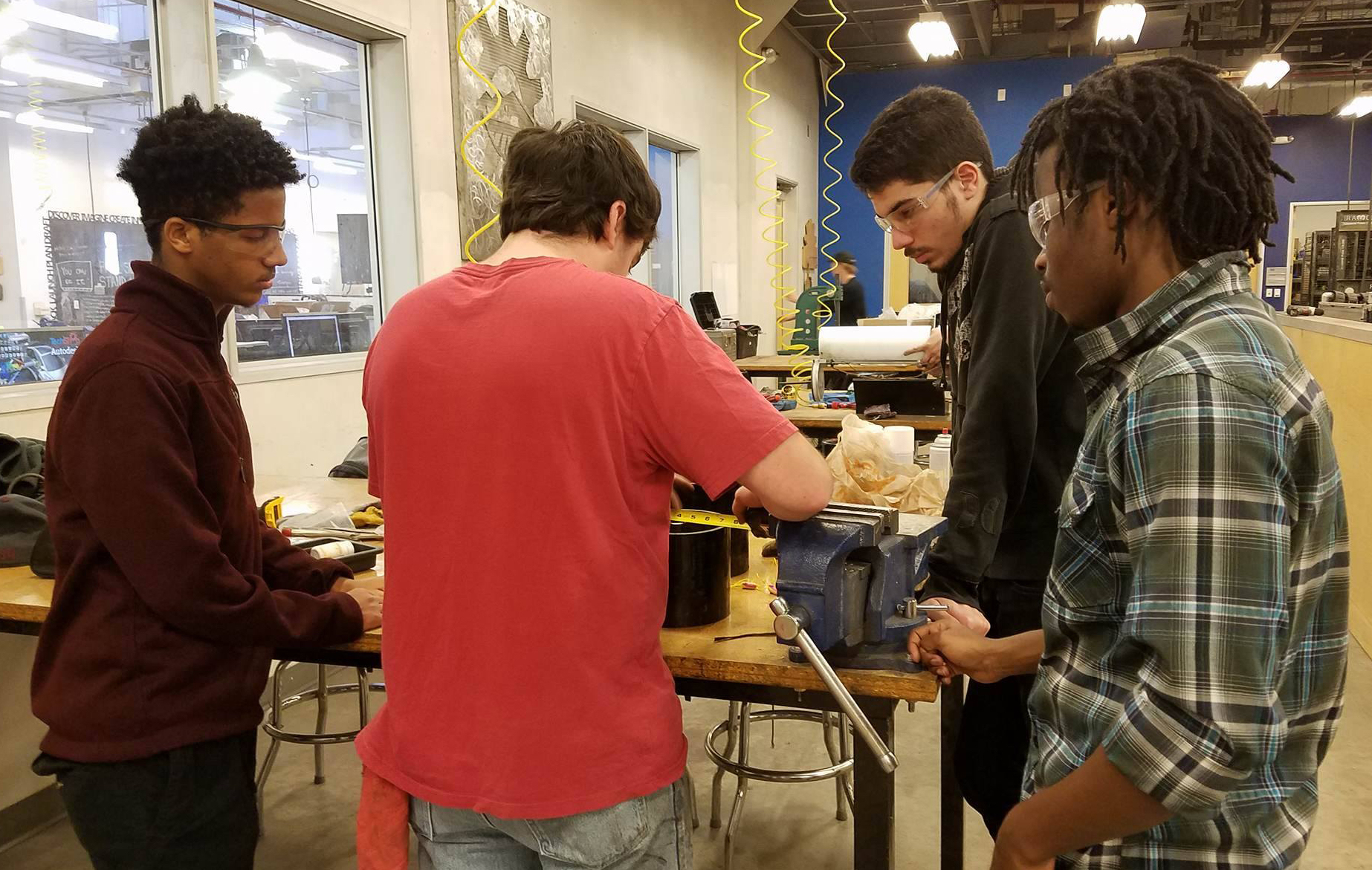 """Photo of four students standing a work table with a caption of """"Gashaw Bizana (far left), Alek Cook (center left), Alessandro Laspina  (center right) and Wakhile Shongwe (far right) working on manufacturing of the team's prototype design of the auger. Photo courtesy of Next Level Devils"""""""