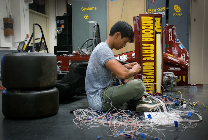 "Photo of student sitting on ground working on wiring of car. caption is ""Engine crew member Gavin Charoenmin is pictured working on the wiring harness for ASU Formula SAE team's race cars. Vehicle undergo extensive technical inspections as part of the international Formula SAE competition. Photographer: Alexander Nie/ASU"""