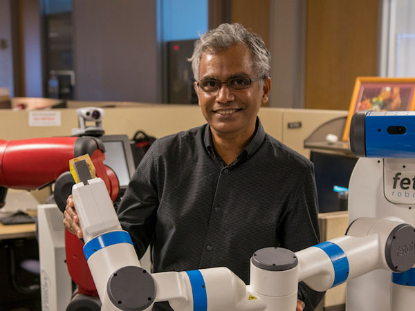 Subbarao Kambhampati poses with one of his lab's robots.