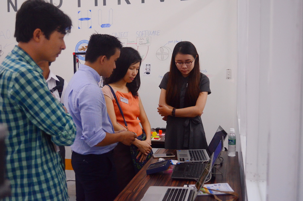 Photo of four people standing and looking at a laptop computerinside of the Maker Innovation Space in Ho Chi Minh City's Saigon Hi-Tech Park