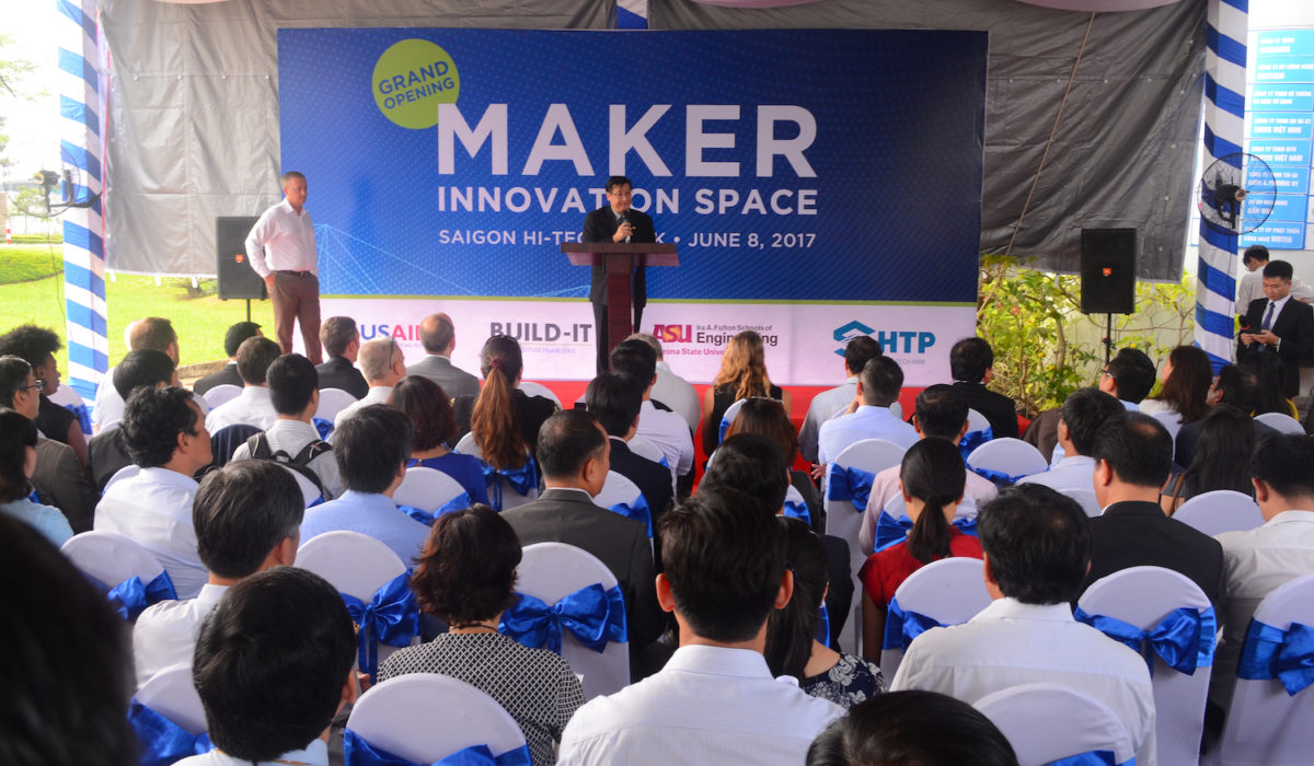 Photo of two men on a stage in front of a crowd. Caption is Le Hoai Quoc, president of the Saigon Hi-Tech Park, welcomes guests to the Maker Innovation Space at the June 8 launch in Ho Chi Minh City, Vietnam. Photo courtesy of BUILD-IT