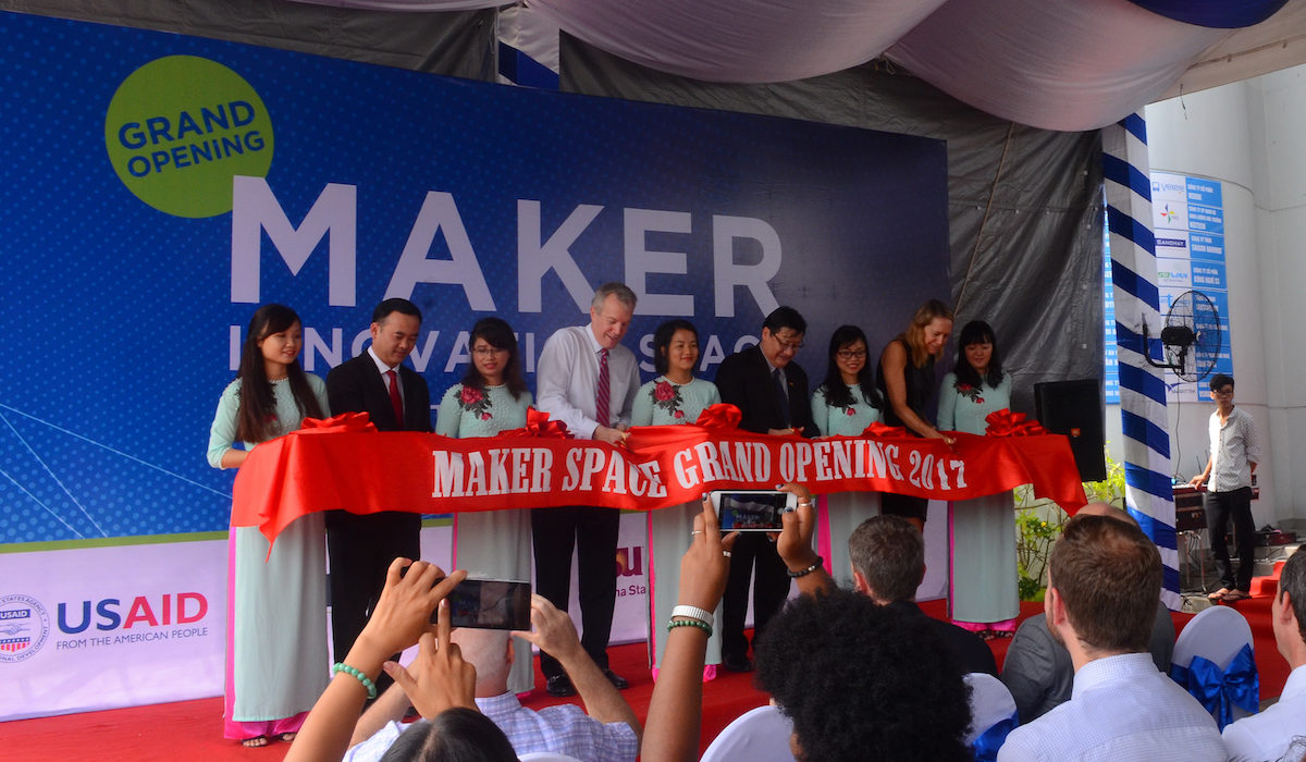 "Photo of nine people behind a red ribbon that say Maker Space Grand Opening 2017. Caption is ""U.S. Ambassador to Vietnam Ted Osius (fourth from right) leads the ceremonial ribbon cutting with Tran Nam Tu (second from left), vice director general, Department of Science and Technology, Ministry of Education and training, Le Hoai Quoc (fourth from right), and Mary Tarnowka (second from right), U.S. consul general. Photographer: Quynh Giao"""