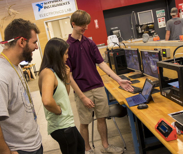 """Photo of three students standing in front of a laptop computer with a caption of """"Patrick Hull (right) shows off his design of the drill exhaust escape and drill tether to Brittany Nez (center) and Christian Sclafani (left). Photographer: Marco-Alexis Chaira/ASU"""""""