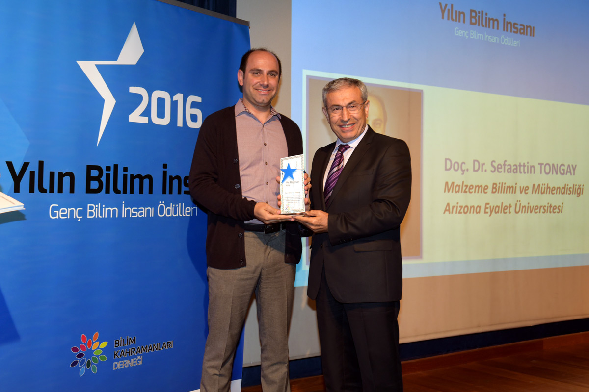 "Photo of man being given an award with a caption of ""Sefaattin Tongay poses with the president of Bahcesehir University at the Heroes of Science Association's award ceremony. Photographer: Özlem Mutlu Doğan"""