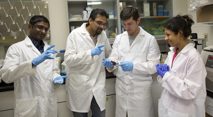 Photo of four people standing in lab coats