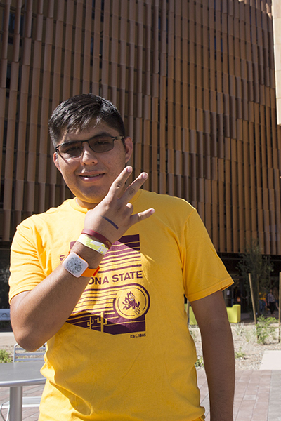 A young man with glasses poses for a photo in front of the new engineering dorm.