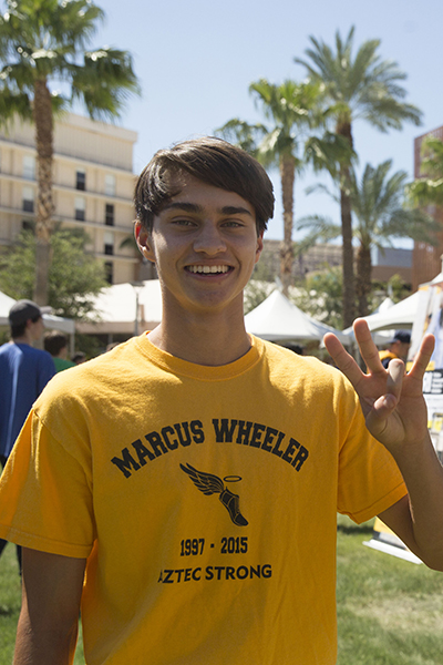 A young man dressed in a bright gold shirt shows his sun devil pride.
