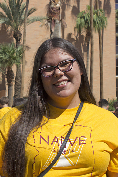 "A young woman in a gold shirt that reads ""Native Sun Devil"" smiles for a photo."