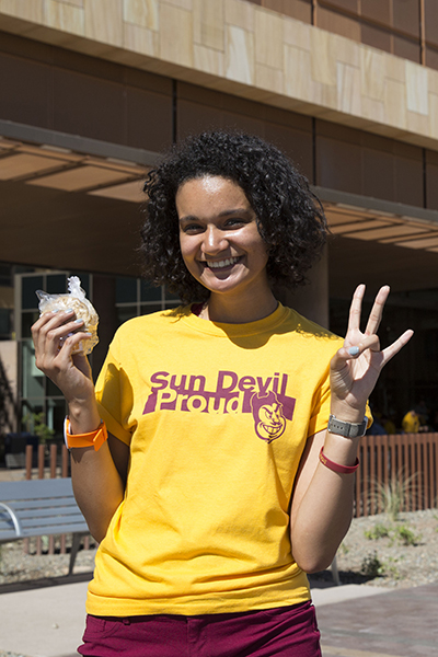 """A young lady in a gold shirt reading """"Sun Devil Proud"""" holds up an ice cream sandwich and ASU's hand symbol, the pitchfork."""