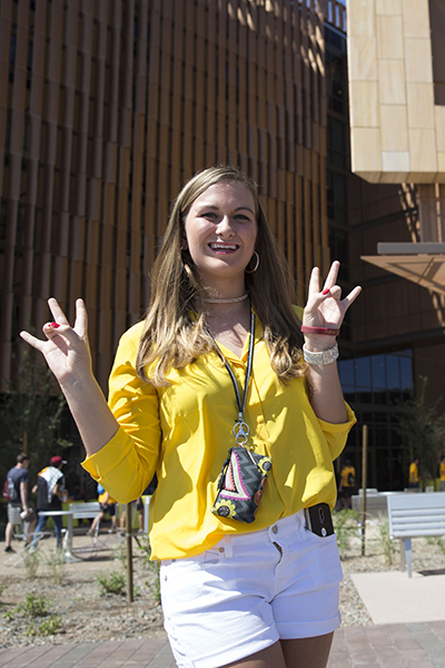 A young woman in yellow throws up double pitchforks — ASU's hand signal.