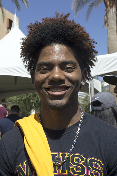 A young man with a soul patch and curly hair smiles for a portrait.