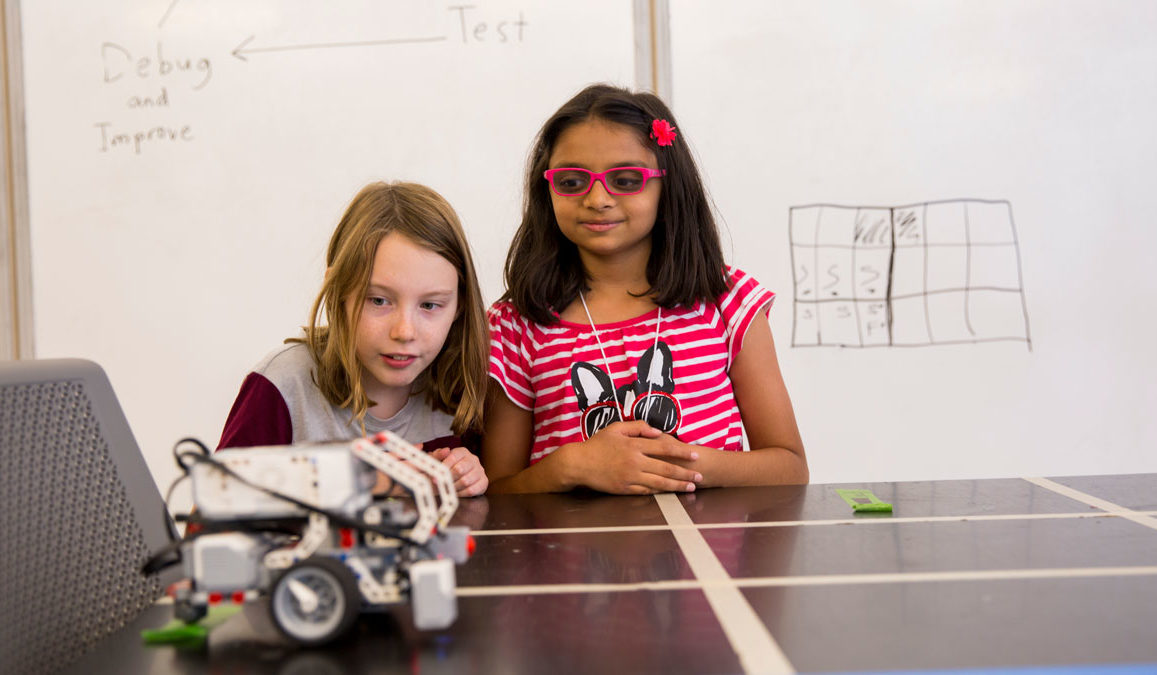 Two girls watch a robotic car on a table.