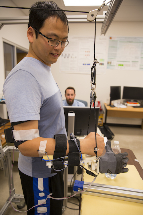 Assistant Research Professor Qiushi Fu is shown demonstrating a synergy-based prosthetic hand