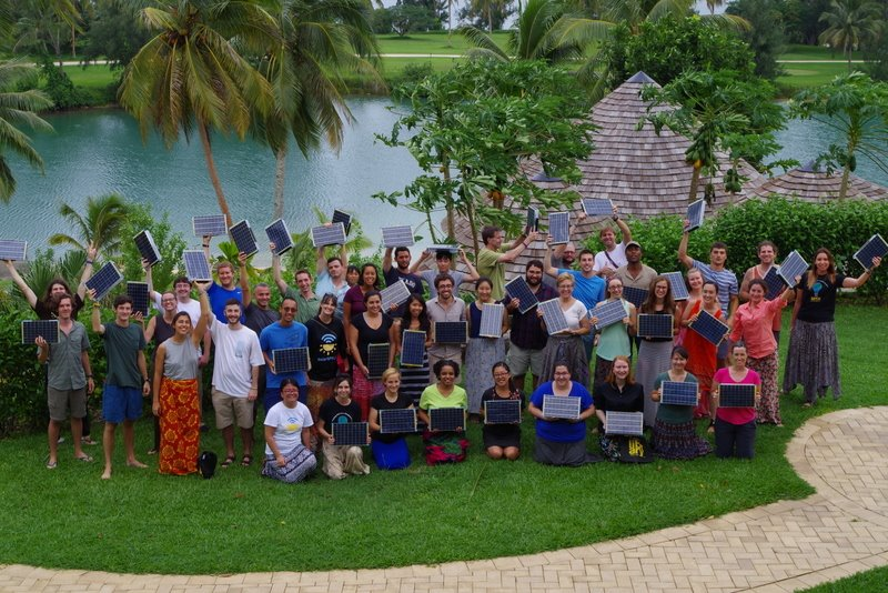 Photo of more than 40 people holding SolarSPELL devices. Caption: The SolarSPELL team trained incoming Peace Corps Volunteers in Vanuatu. Photo courtesy of Brittany Blevins