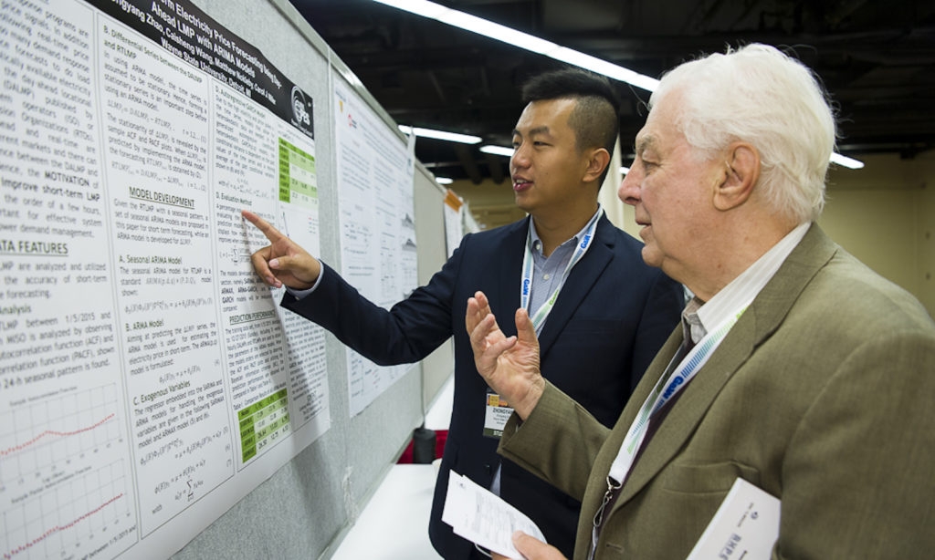 Photo of two men looking at a poster. Caption: George Karady representing the U.S.-Pakistan Centers for Advanced Energy USPCAS-E and ASU, surveys posters at the IEEE PES 2017 General Meeting . Photo credit: IEEE PES