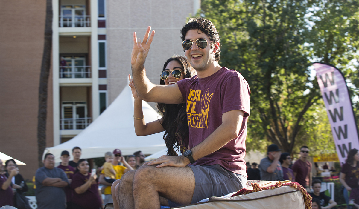 Photo of Mark Huerta riding in the back of a car. Caption: Mark Huerta, founder of 33 Buckets and a doctoral student in the engineering education systems and design program, served as marshal at the ASU Homecoming Parade, which kicked off the Homecoming Block Party, Oct. 28, 2017. Photographer: Jessica Hochreiter/ASU