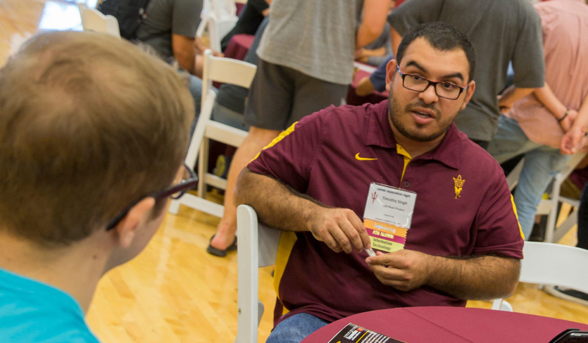 An ASU engineering alumni talks with a student.