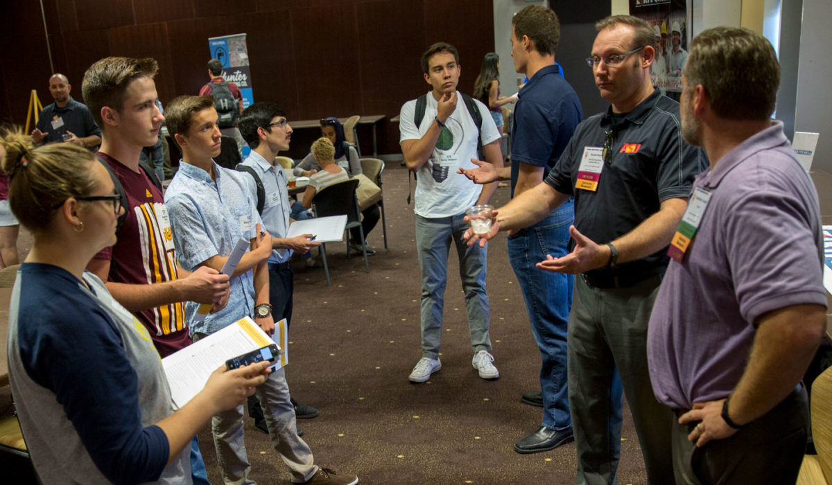 An industry professional stands and talks with a group of engineering students.