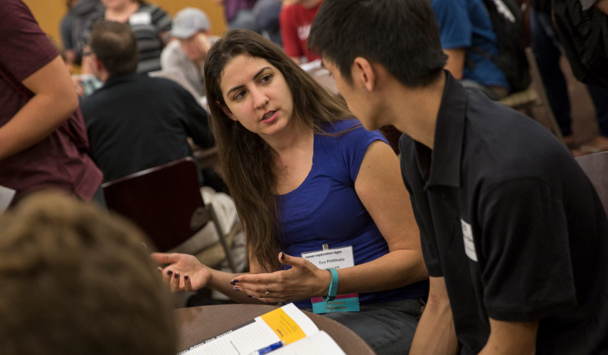 An industry professional engineer gestures with her hands as she talks to a student.